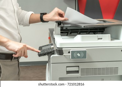 Man copying paper from Photocopier with access control for scanning key card