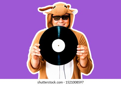 Man in cosplay costume of a cow with gramophone record isolated on purple background. Guy in the animal pyjamas sleepwear. Funny photo with party ideas. Disco retro music.