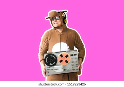 Man in cosplay costume of a cow with reel tape recorder isolated on purple background. Guy in the animal pyjamas sleepwear. Funny photo with party ideas. Disco retro music.
