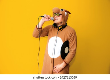 Man in cosplay costume of a cow singing karaoke. Guy in the funny animal pyjamas sleepwear holding microphone. Funny photo. Party ideas. Disco music.