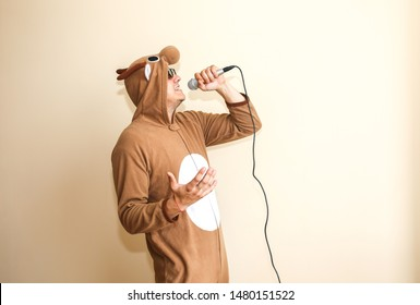 Man in cosplay costume of a cow singing karaoke. Guy in the funny animal pyjamas sleepwear holding microphone. Funny photo with reel tape recorder. Party ideas. Disco retro music.