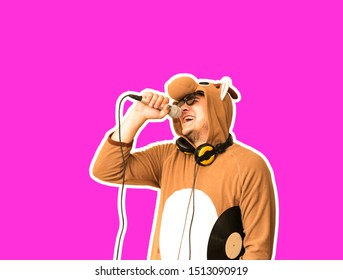 Man in cosplay costume of a cow singing karaoke isolated on purple background. Guy in the funny animal pyjamas sleepwear holding microphone. Funny photo. Party ideas. Disco music.