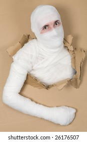 Man in costume mummy looking through hole in cardboard