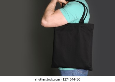 Man with cotton shopping eco bag on grey background. Mockup for design