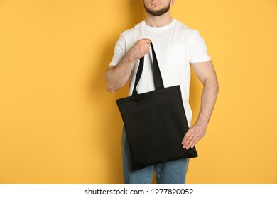 Man with cotton shopping eco bag on color background. Mockup for design