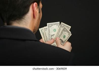 Man count dollars