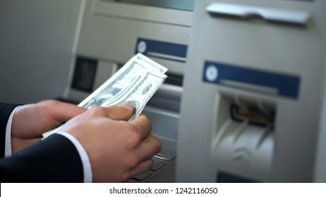 Man counting dollars withdrawn from ATM, 24h service, easy banking operation