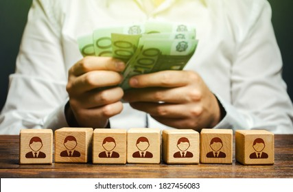 A man is counting euro money in his hands over blocks with symbols of employees. Wage fund. Accounting and budgeting. Payday. Expanding a profitable business, recruiting and training employees.