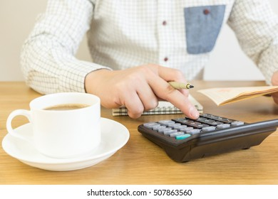 A man counting the money in the bankbook and making notes with a cup of coffee on the table