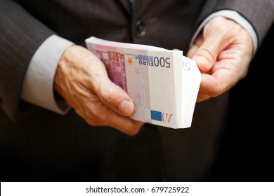 A man counts the money in a bundle of banknotes of 500 euros. Shallow focus. Business or financial concept.