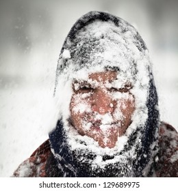 Man covered by snow in heavy snowstorm.