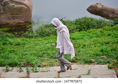 Man covered with a large cloth walking to the riverbank in Hampi, India