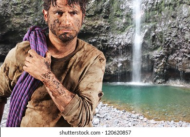 A man covered in mud with a rope, trying to survive, with a green lake in the background