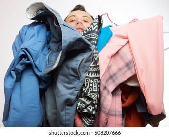 Man covered of stack dirty clothes. One men holding a lot of dresses isolated on white