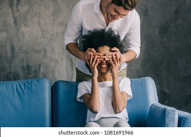 Man covering eyes of african american girlfriend sitting on sofa