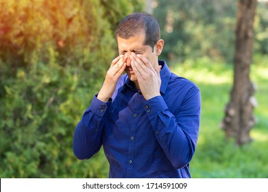 Man covering eyes by hand of bright sunlight