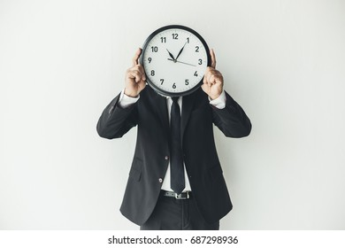 man covering face with clock on light background