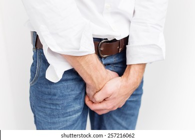 Man covering his crotch with both hands
