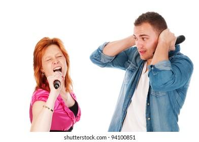 man covering his ears because girlfriend sings too loud