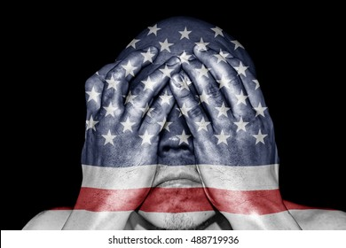 A man covering his eye with his hand with imprint of an American flag for the concept: Justice is blind in United States of America.