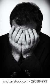 man covering his face with his hands. black and white image