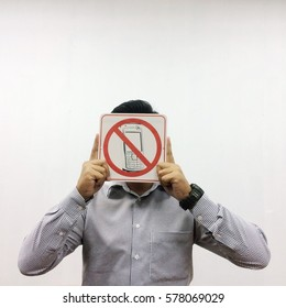 """a man covering his face and holding a sign """"No Handphone """" against backdrop of white walls"""