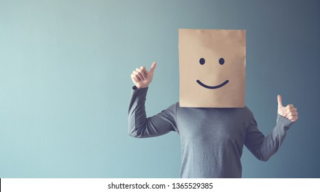 Man covering his face with a smiling face emoticon, copy space.