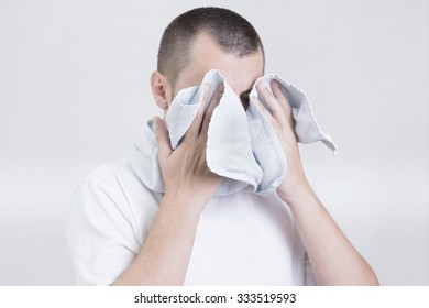 Man covering his face with a towel