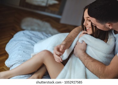Man covering his girlfriend with blanket in the bedroom