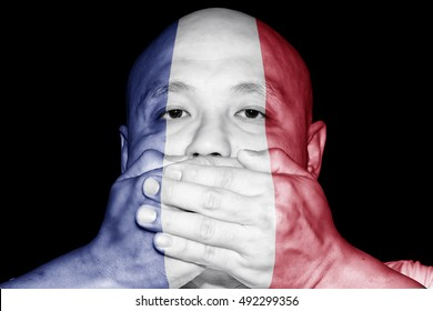 A man covering his mouth with his hand with imprint of a French flag for the concept: No gossip in France.