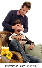 A man covering a man's eyes while he tries to watch TV