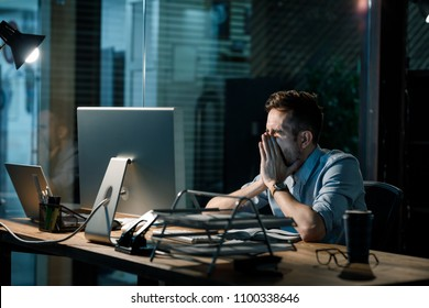 Man covering mouth while yawning at table in dark office having overtime.