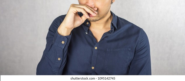 Man covering nose by hand, smell something bad expression