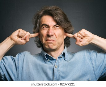 A man covers his ears with his hands. Suffering from a loud sound.