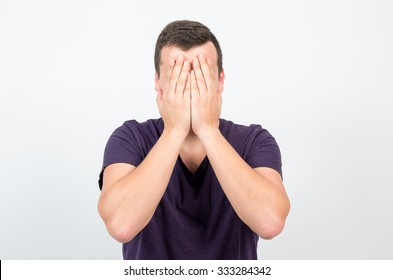 man covers his eyes