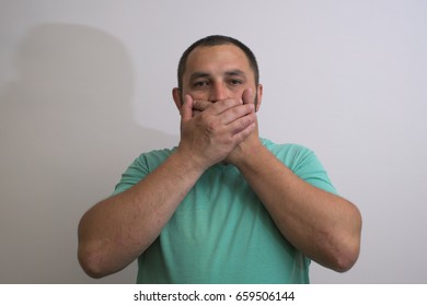 man covers his mouth with his hands, fear, does not want to roar, laughing