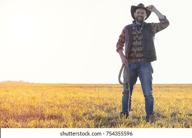 A man in a cowboy hat and a loso in the field. American farmer in a field wearing a jeans hat and with a loso. A man is walking across the field in hat