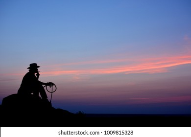 Man in cowboy hat sitting on a rock like western film background at sunrise or sunset,  silhouette concept. Sitting on the hill with cigar and whip, smoking and thinking.