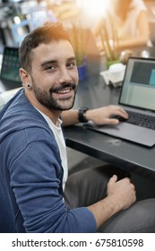 Man in coworking office working on laptop
