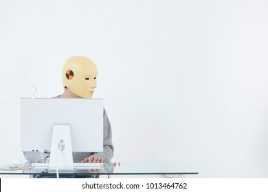Man in crash dummy mask working at computer