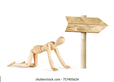 Man is crawling in the direction of the road sign. Abstract image with a wooden puppet
