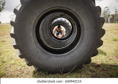 Man crawling through the tire during obstacle course in boot camp