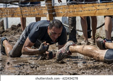 A man crawling under barbed wire during strength race Legion Run held  in Sofia, Bulgaria on 26 July 2014
