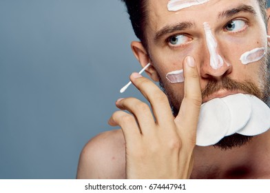 Man with cream on his face, eared sticks, cotton pads