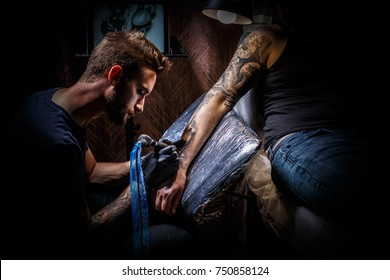 Man creating tattoo on hand with it in the salon