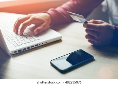 Man with credit card in hand and smartphone using laptop. Online payment (Intentional sun glare)