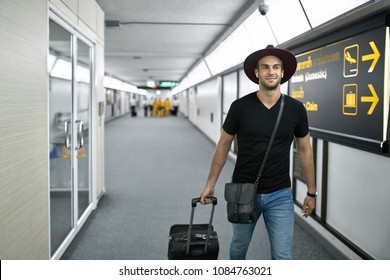 Man in a crimson hat with a black travel bag walks in the airport. He wears a black T-shirt, shoulder pouch and blue jeans. Man looks forward with a smile. Horizontal.