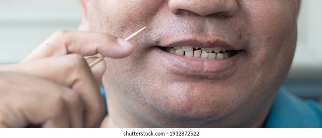 man with crooked teeth using toothpick, concept of oral care, tooth care, bad breath