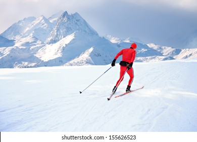 A man cross-country skiing in front of winter landscape