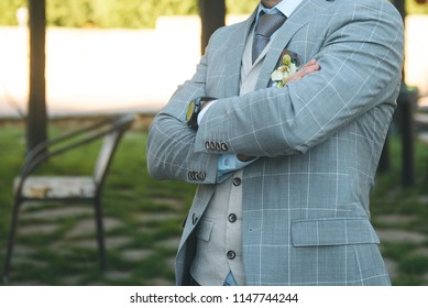 man with crossed hands in suit standing at cafe